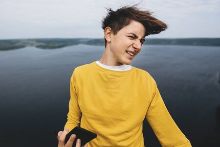 Stylish hipster teenager taking selfie on phone and having fun on top of rock mountain with amazing view on river. Young guy in yellow pullover exploring and traveling. Copy space