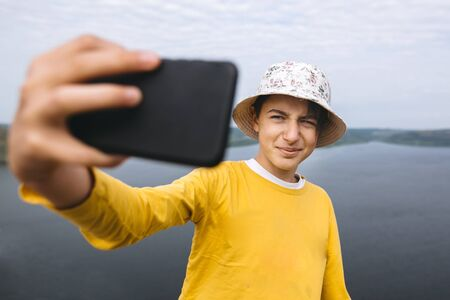 Hipster teenager taking selfie on phone while standing on top of rock mountain with amazing view on river. Young stylish guy in yellow pullover and hat exploring and traveling. Copy space
