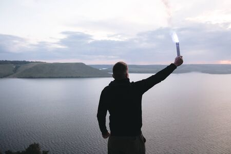 Ultras hooligan holding blue flare torch in hand, standing on top of rock mountain in evening with amazing view on river. Atmospheric moment. Copy space