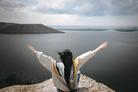 Back of stylish hipster girl sitting on top of rock mountain with beautiful view on river. Young tourist woman with windy hair relaxing on cliff. Travel and wanderlust. Copy space