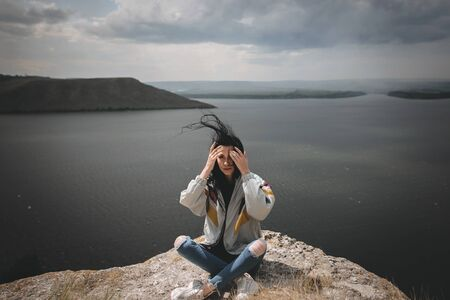 Stylish hipster girl with windy hair sitting on top of rock mountain with beautiful view on river. Young tourist woman relaxing on cliff. Atmospheric moment. Copy space