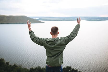 Hipster traveler standing on top of rock mountain and raising hands up,  enjoying amazing view on river. Stylish guy in green windbreaker exploring and traveling. Atmospheric moment Фото со стока