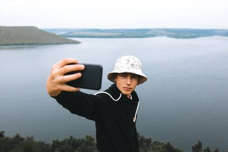 Hipster teenager taking selfie on phone while standing on top of rock mountain with amazing view on river. Young stylish guy exploring and traveling. Atmospheric moment. Copy space