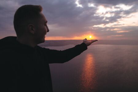 Hipster traveler enjoying amazing sunset view on river and holding sun on hand while standing on top of rock mountain. Atmospheric funny moment. Copy space Фото со стока