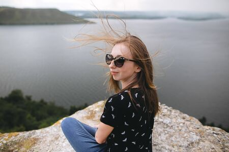 Happy girl in sunglasses sitting on top of rock mountain with beautiful view on river. Young tourist woman with windy hair relaxing on cliff. Summer vacation. Copy space
