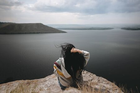 Back of stylish hipster girl sitting on top of rock mountain with beautiful view on river. Young tourist woman with windy hair relaxing on cliff. Atmospheric moment. Copy space Фото со стока
