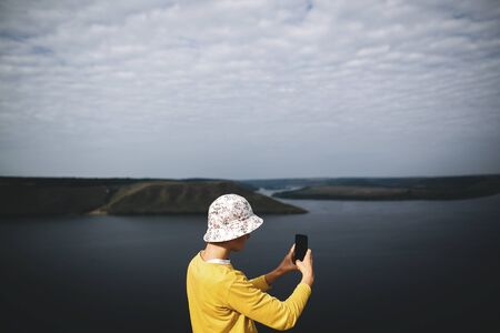 Hipster teenager taking photo on phone of amazing view on river while standing on top of rock mountain. Young stylish guy exploring and traveling. Atmospheric moment. Copy space Фото со стока