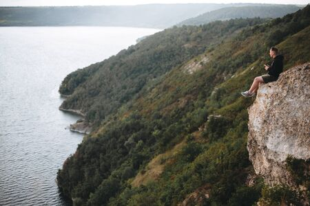 Hipster traveler sitting on top of rock mountain and enjoying amazing view on river. Young guy exploring and traveling. Atmospheric tranquil moment. Copy space Фото со стока