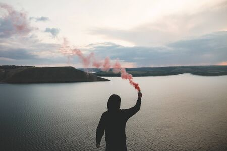 Stylish hipster holding red smoke bomb in hand, standing on top of rock mountain with amazing sunset view on river. Atmospheric moment. Traveler guy with smoke. Copy space