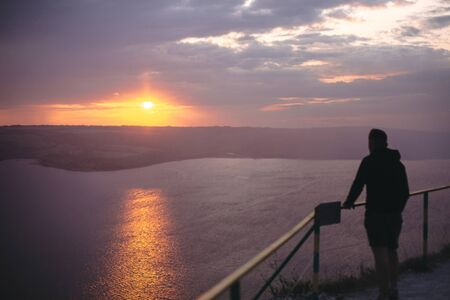 Hipster traveler standing on top of rock mountain and enjoying amazing sunset view on river. Stylish guy in windbreaker exploring and traveling. Atmospheric tranquil moment. Copy space Фото со стока