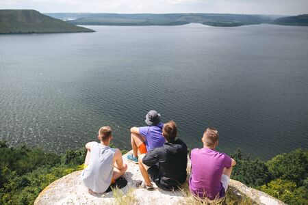 Group of hipster travelers sitting on top of rock mountain and enjoying  amazing view on river. Young guys explorers relaxing and traveling. Atmospheric tranquil moment. Copy space