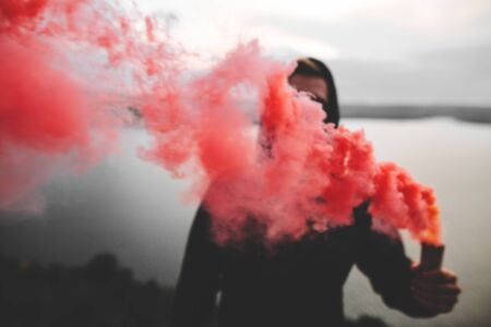 Red smoke bomb. Blurred image of ultras hooligan holding  smoke bomb in hand, standing on top of rock mountain with amazing view on river. Atmospheric moment. Copy space Фото со стока