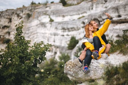 Happy hipster couple taking selfie on phone on top of rock mountain. Tourist couple hugging on windy cliff among trees and making photo. Travel and wanderlust. Copy space Фото со стока