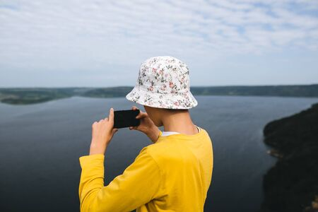 Hipster teenager streaming live while standing on top of rock mountain with amazing view on river. Young stylish guy exploring and making video of travel. Copy space