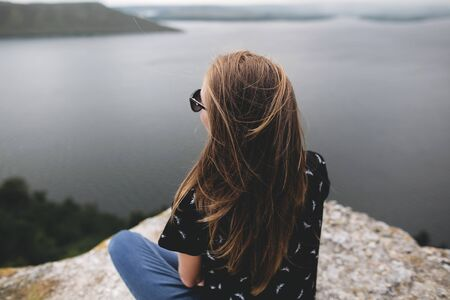 Back of hipster girl sitting on top of rock mountain with beautiful view on river. Young tourist woman with windy hair relaxing on cliff. Travel and wanderlust. Copy space