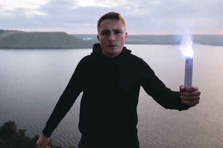 Brutal man in black windbreaker holding blue flare torch in hand, standing on top of rock in evening with view on river.  Ultras hooligan with fire signal bomb. Atmospheric moment