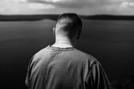 Loneliness concept. Hipster traveler standing alone on top of rock mountain with amazing view on river .Black and white photo. Atmospheric tranquil moment. Copy space