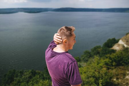 Stylish hipster traveler in purple shirt standing on top of rock mountain with amazing view on river. Young brutal guy exploring and traveling, back view. Copy space