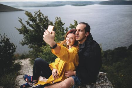 Happy hipster couple taking selfie on phone on top of rock mountain with beautiful view on river. Tourist couple hugging on windy cliff and making photo. Travel and wanderlust. Copy space
