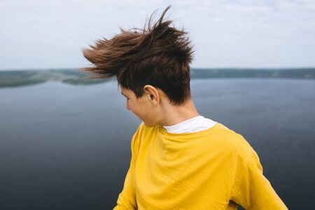 Stylish hipster teenager having fun and waving hair on top of rock mountain with amazing view on river. Young guy in yellow pullover exploring and traveling. Copy space