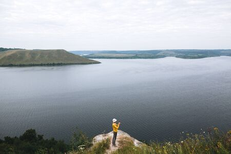 Hipster teenager in yellow pullover standing on top of rock mountain and looking on river, view from back. Young stylish guy exploring and traveling. Atmospheric tranquil moment