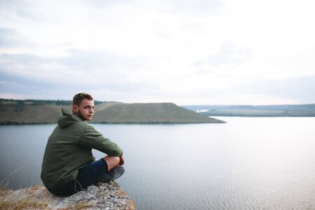 Hipster traveler sitting on top of rock mountain and enjoying amazing view on river. Stylish guy exploring and traveling. Atmospheric tranquil moment. Copy space
