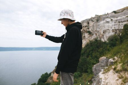 Hipster teenager streaming live while standing on top of rock mountain with amazing view on river. Young stylish guy exploring and traveling. Atmospheric moment. Copy space