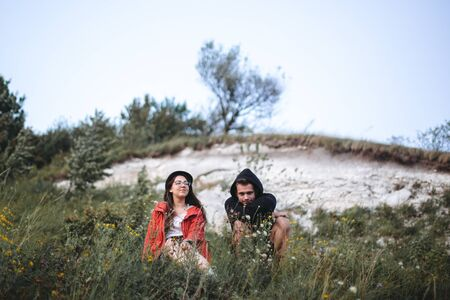 Hipster couple sitting on top of rock mountain in grass and enjoying amazing view on river in sunset. Stylish travelers exploring and traveling. Atmospheric tranquil moment. Copy space Фото со стока