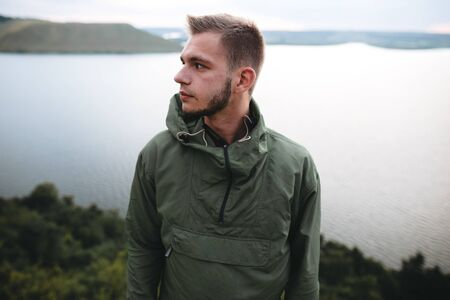 Hipster traveler standing on top of rock mountain and enjoying amazing view on river. Stylish guy in green windbreaker exploring and traveling. Atmospheric tranquil moment. Copy space Stok Fotoğraf