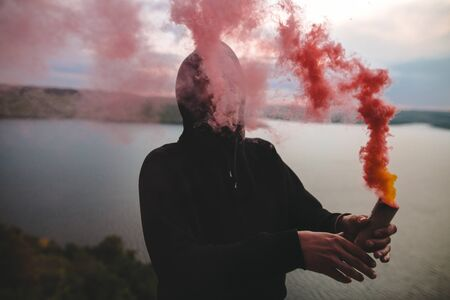 Ultras hooligan holding red smoke bomb in hand, standing on top of rock mountain with amazing view on river. Atmospheric moment. Traveler guy with smoke. Copy space
