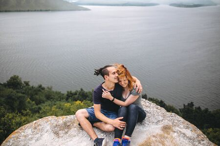 Happy hipster couple sitting on top of rock mountain with beautiful view on river. Tourist couple hugging and smiling on windy cliff. Traveling together. Copy space