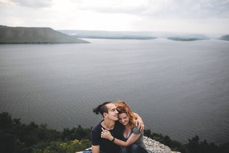 Happy hipster couple gently embracing on top of rock mountain with beautiful view on river. Tourist couple hugging on windy cliff, tranquil moment. Travel and wanderlust. Copy space