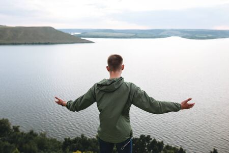 Hipster traveler standing on top of rock mountain and raising hands up,  enjoying amazing view on river. Stylish guy in green windbreaker exploring and traveling. Atmospheric moment Stok Fotoğraf