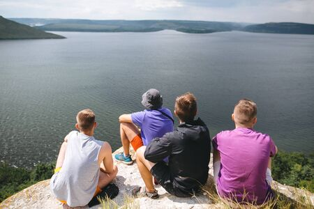 Group of hipster travelers sitting on top of rock mountain and enjoying  amazing view on river. Young friends explorers relaxing and traveling. Atmospheric tranquil moment. Copy space Stok Fotoğraf
