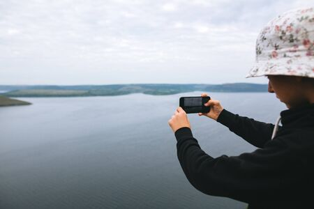 Hipster teenager taking photo on phone of amazing view on river while standing on top of rock mountain. Young stylish guy exploring and traveling. Atmospheric moment. Copy space Stok Fotoğraf