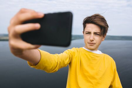 Stylish hipster teenager taking selfie on phone while standing on top of rock mountain with amazing view on river. Young guy in yellow pullover exploring and traveling. Copy space