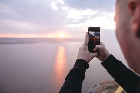 Hipster traveler taking photo on phone of amazing sunset view on river while standing on top of rock mountain. Atmospheric  moment. Copy space. Travel and explore Stok Fotoğraf