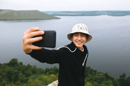 Hipster teenager taking selfie on phone and smiling, standing on top of rock mountain with amazing view on river. Young stylish guy exploring and traveling. Atmospheric moment. Copy space