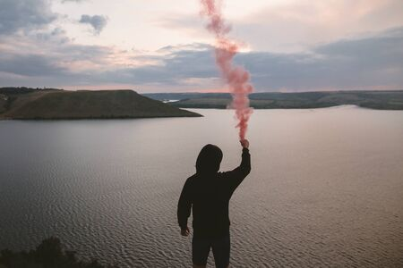 Ultras hooligan holding red smoke bomb in hand, standing on top of rock mountain with amazing sunset view on river. Atmospheric moment. Traveler guy with smoke. Copy space