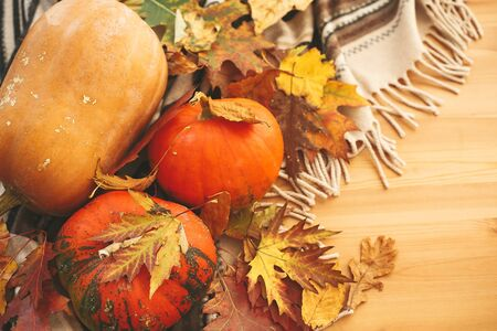 Pumpkins  with fall leaves on brown blanket on background of wooden table. Hygge lifestyle, cozy autumn mood. Happy Thanksgiving. `Happy Halloween Stok Fotoğraf
