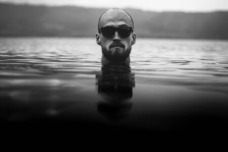 Brutal bearded man in sunglasses emerge in lake waves. Man head above water in lake in rainy foggy day, atmospheric moment. Wanderlust. Creative black and white photo