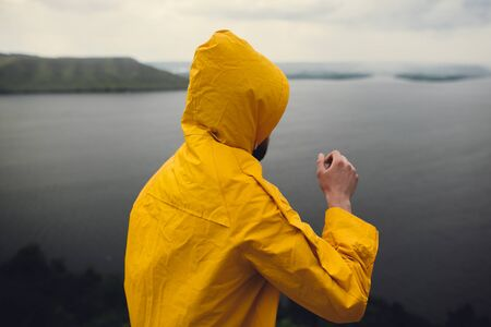 Hipster traveler in yellow raincoat standing on cliff and looking at lake in windy moody day. Wanderlust and travel concept. Man hiking in Norway on foggy day. Atmospheric moment Фото со стока