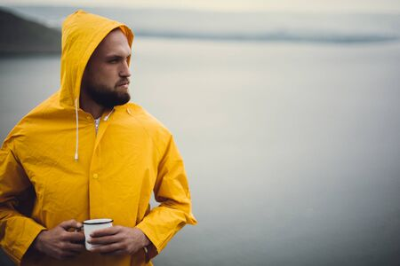 Hipster traveler in yellow raincoat holding metal mug and standing on cliff in rainy windy day with view on lake. Wanderlust and travel. Brutal bearded man hiking. Copy space