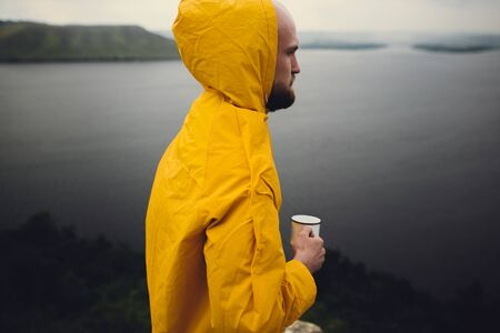 Traveler in yellow raincoat holding metal mug and standing on cliff  in rainy windy day with view on lake. Wanderlust and travel. Hipster man hiking in Norway. Atmospheric moment 스톡 콘텐츠