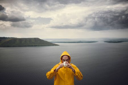Atmospheric moment. Hipster traveler in yellow raincoat holding metal mug and standing on cliff in rainy windy day with view on lake. Wanderlust. Brutal bearded man hiking. 스톡 콘텐츠