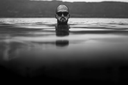 Brutal bearded man with cigarette and in sunglasses emerge in lake. Man head smoking above water in lake in rainy foggy day, atmospheric moment. Wanderlust. Creative black and white photo
