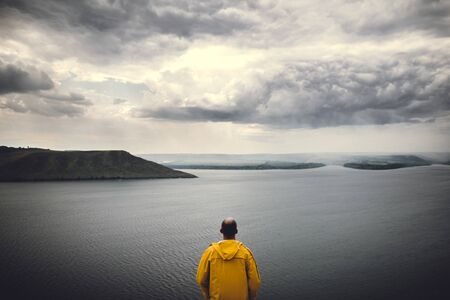 Wanderlust and travel concept. Hipster traveler in yellow raincoat standing on cliff and looking at lake in windy moody day. Man hiking in Norway on foggy day. Atmospheric moment