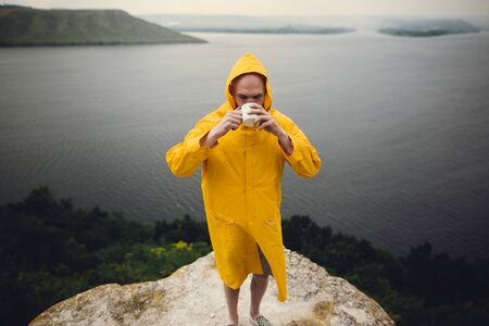 Wanderlust. Hipster traveler in yellow raincoat holding metal mug and standing on cliff  in rainy windy day with view on lake. Hipster man hiking in Norway. Atmospheric moment Фото со стока