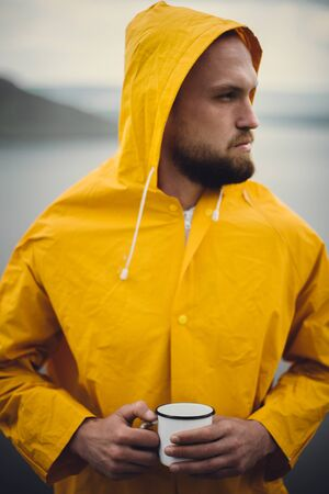Traveler in yellow raincoat holding metal mug and standing on cliff  in rainy windy day with view on lake. Wanderlust and travel. Hipster man hiking in Norway. Atmospheric moment Banco de Imagens