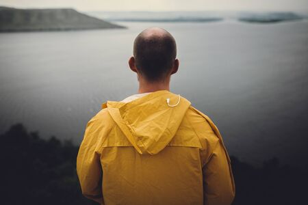 Traveler in yellow raincoat standing on cliff and looking at lake in rainy windy day. Wanderlust and travel concept. Hipster man hiking in Norway on foggy day. Atmospheric moment